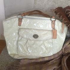 Patent leather coach bag Signature patent leather cream colored coach bag with tan straps, bag has some wear as outside has a small pen mark as show in the photo to the left of bag, and bag has slight discoloration, inside has a few stains as shown, tan straps are in good condition, overall bag is in decent condition Coach Bags
