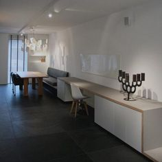 Amstelveen 2009ontwerp: studio RuimLang meubel dat in hoogte verspringend schijnbaar zwevend tegen een lange muur is gemonteerd. In het meubel zijn een bankje, een bureau en kasten geïntegreerd. Gemaakt van berken multiplex met desktop linoleum en gelakt mdf.