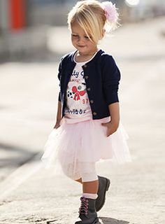 cute little girl: updo, hair flower, dark jacket, pushed-up sleeves, tulle skirt, boots