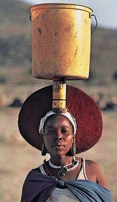 Africa | Zulu woman carrying water. South Africa | ©Thomas Nebbia; National Geographic February 1984. The water bucket is balanced on top of an old can for insect spray.