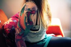 With its graceful body and long, elegant tail feathers, a phoenix makes for a great tattoo on a large scale, whether it is inked as a full back tattoo or a full sleeve, like this girl's arm tattoo. The phoenix tattoo is pretty large and colorful, incorporating blues, reds, oranges and ...