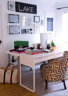 Chic shared office features Face to face desks with Ikea Micke Desk paired with fretwork chair situated in front of art wall and atop gray carpeting.