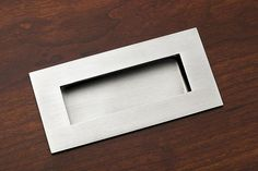 A rectangular, recessed pull finished in Satin Stainless Steel.