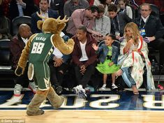 High-five: The adorable youngster seemed happy to interact with the Milwaukee Bucks mascot Bango