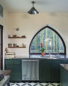 arched window, deep green cabinets, subway tile to ceiling