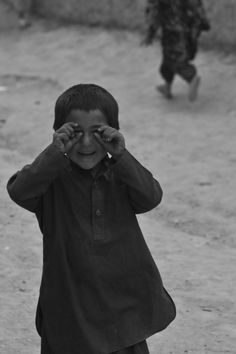 "forweareallnothing:    I took this photo while on patrol in a village in Parwan Province, just outside of Bagram Airfield, Afghanistan. Usually when I raise my camera up to my eye the children run off, fearing for their lives. This guy kept peeking around the corner taking ""pictures"" of me. I'm so glad I could capture this moment"
