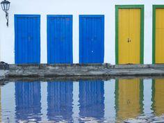 Biele domy sú postavené na mohutných kameňoch, ale ich uniformnosť rozbíjajú farebné dvere a okná.