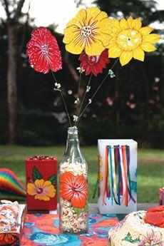 Recorte as flores da chita, respeitando o desenho do próprio tecido, e cole-as em garrafas de vidro transparentes. Para fazer o arranjo, use arame como base e fixe as flores na ponta (corte-as duas vezes no tecido para fazer frente e verso e coloque entretela no meio para deixá-la armada). Fixe pipocas nos caules de arame. Para fazer o pote vermelho, que guarda amendoim torrado, recorte embalagens de leite longa vida. Lave-as muito bem, seque e faça o revestimento da caixa com tecido…