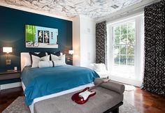 Inspiring bedrooms accent wall and ceiling. A colored ceiling, dark blue wall wallpaper, blue sheets and dark blue pillows. Also a grey loveseat with an acoustic guitar on it.