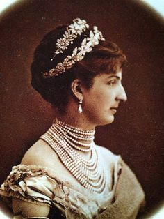 Queen Margherita of Italy wearing the Mellerio laurel tiara and another floral tiara on her head.