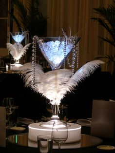 Great Gatsby themed centerpiece. A martini vase on a light base with beads and feathers
