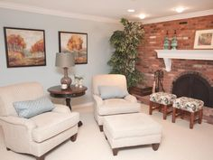 STOOLS ...... DIY ....An exposed brick fireplace fills one wall in this traditional living room that features two cream chairs, a matching ottoman and two paisley stools. Two framed paintings of autumnal outdoor scenes on the wall pick up on the color of the brick to further warm up the space.