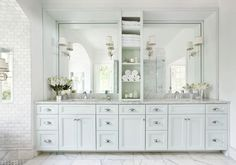 Love this custom vanity for a master bathroom! Appearance of entirely framed wall with towel storage tower separating his and her sinks. Spacious master bath with marble flooring and shaker cabinets painted a pale shade of turquoise by Mark Williams