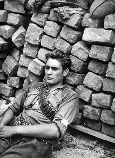 Portrait of a member of the French Resistance, who rests against a barricade erected on the streets of Paris, during a lull in street battles with the occupying German forces. Paris, France. August 1944. Photograph by Robert Doisneau.