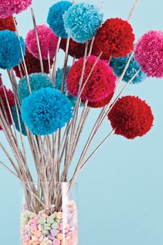 Pom-pom Flowers-To make each pom-pom, wrap yarn around the palm of your hand until you have a thick loop. Slide the loop off your hand, then tightly knot a 10-inch piece of yarn around its center. You'll have a bundle of yarn that is looped at either end. Cut through the loops & shake out your pom-pom, & trim until it is the size you desire. Use a glue gun to attach pom-pom to a dowel or thin branch. Arrange pom-pom flowers in a vase filled with candy hearts.