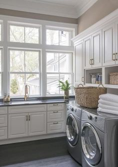 Chic cottage laundry room features a silver front-load washer and dryer tucked under cabinets fitted with open shelving.