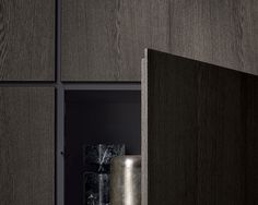 Detail of wall composition with glossy moka lacquered structure, back panels and Slim leaf doors in cenere oak.