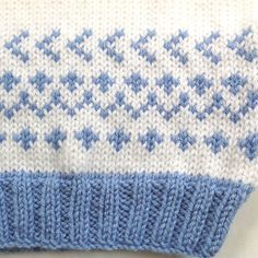 Age 6 to 12 months. This little sweater, knitted in a medium weight, acrylic yarn, is suitable for both baby boys and girls. It is white with contrasting ribbings in a nice mid- blue color and with a cute Fair Isle pattern on the front and back. An ideal second size baby shower gift.