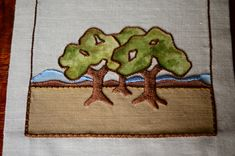 """Arts & Crafts style Oak Trees Table Runner, Craftsman, Mission $275, via Etsy. Our """"Trees"""" design worked in beautiful earth tone threads. Each tree is hand-painted (not stenciled) in tones of olive greens, golds and brown. Stitches used include the satin stitch, stem stitch and couching stitch. The valley floor is appliqued  and is ready for the couching stitch. Pictured with a decorate stem stitched hem, which is easy even for the beginning stitcher. Finished dimensions are 14""""Wx42""""L."""