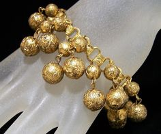 Mid Century dangling beads charm bracelet Small and medium textured gold tone beads are attached to a book chain link chain 6 3/4 inches long, each wire linked beaded charm is 1 inch long Beads are 7 and 11 mm Unsigned, fold over clasp Good vintage condition, a few of the beads have dark spots International buyers welcome, over charges are refunded Priority shipping is offered 121416 Want to see more great bracelets? Click here: https://www.etsy.com/your/shops/...