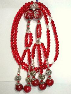 Red Jelly Dounut  This set of Juzu Beads are the traditional 108 beads used in Nichiren Buddhism. Materials used are: red main glass beads enhanced with silver spacers,toppers, and clear glass beads. The four Bodhisattva's are clear white swarovski crystals. The Kyochie Myogo pair are hand blown glass with silver foil enlay strips and the Kosen-rufu ends are red marble.  Price$105.00