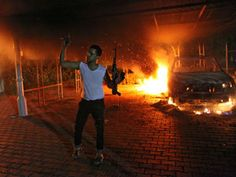 An armed man waves his rifle as buildings and cars are engulfed in flames after being set on fire inside the US consulate compound in…