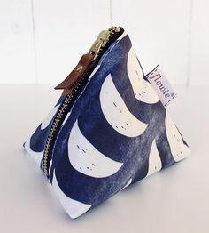 Handy and adorable, this canvas pouch can be used to store all of your small trinkets and treats. Its exterior features a navy and white crescent moon pattern with hazy faded clouds throughout the dark background. The triangle pouch is lined with cotton fabric and secures your goodies with a brass zipper closure. Fill it with the little stuff that accumulates at the bottom of your bag—loose change, your selection of lip balms or jewelry for travel.