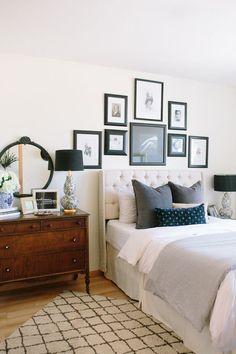 antique dresser   upholstered headboard   gallery wall above bed   target rug   grey and blue bedroom