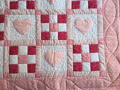 Colcha ou manta para bebê de patchwork em tons de rosa.