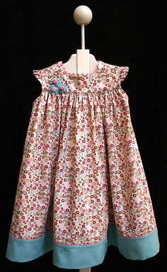 """CC Hillary sundress. I accented with aqua pique and medium bright pink rick rack. . I used 1/2"""" pink pique buttons for the center.  Needed accessories: 3 yds of bright pink medium rick rack, 5/8 yd aqua pique, 3 1/2"""" pink pique buttons."""