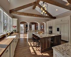 Beautiful two-tone kitchen with vaulted ceiling beams, wood floors, wood and granite countertops, antique white, brown wood .. #hardwoodfloorpics #woodflooring
