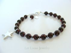 Garnet bracelet, dark red, genuine gemstones sterling silver, star charm, handmade, stack, Let Loose Jewelry, gift for her, under 50   Description: Deep dark garnets make a great, stand out bracelet~ this is a simple, wearable piece featuring 6mm round garnet stones alternating with antiqued, corregated sterling beads. For a little fun there is a big shiny star charm off to the side. Ive finished this bracelet with a large, antiqued, twisted ring and 11mm lobster clasp, total length is 7…