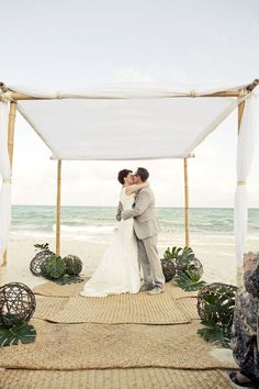 wedding arch with tropical plant leaves and other decor.