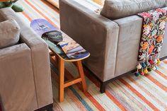 Decoração com personalidade, decoração colorida de sala de estar com obras de arte, manta colorida, tapete e sofá cinza.