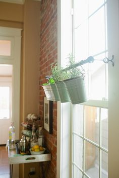 This is a great idea! Using a rod across a window for hanging plants! Not only does it provide light, it prevents from cluttering a table or windowsill.