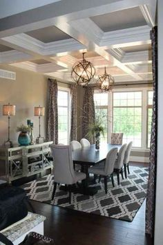 Two globe chandeliers hang above the dining room table. Design and Furnishing by Design Source Interiors.