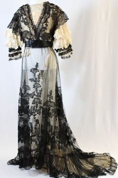 """Early 1900's dress. Made in Paris and imported by Mme Gully of New York. Features beautiful lace throughout in an intricate floral pattern, lined with silk and Georgette. Ruffled sleeves with nude lace. Approximate measurements: Bust - 34"""" Waist - 28""""  