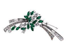 Länge: ca. 5,5 cm. Gewicht: ca. 9,8 g. WG 750. Um 1960. Brosche in Form eines stilisierten Blütenzweigs mit Smaragden im Navetteschliff, zus. ca. 0,8 ct, und...