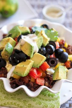 Paleo Taco Bowl with ground beef, eggs, tomatoes, bell peppers, olives, avocado