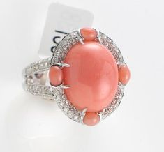 A coral, diamond and eighteen karat white gold ring