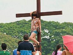 Netizens outraged by photo of woman posing on a cross