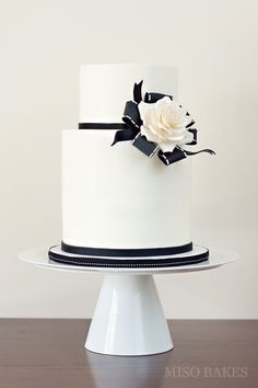 Love this cake...A brooch made of sugarpaste black ribbons and sugarpaste rose serve as a contrast against a smooth double barrel buttercream cake.