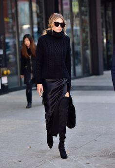 Gigi Hadid wears a chunky black Nili Lotan sweater and silk slit skirt with over-the-knee Stuart Weitzman boots