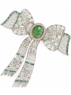 A diamond, nephrite and green stone articulated bow brooch, centering a bezel-set oval cabochon nephrite, with round and baguette-cut diamonds and green stone accents; estimated total diamond weight: 6.20 carats; mounted in platinum; length: 2 3/4in.