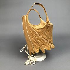 LOT 62 TAN LINEN CORSET, c. 1800 Back lacing with shortened torso silhouette having shoulder strap, center front is notched with fixed laces, top edge bound in suede, includes custom mount. Under (Back lace replaced) excellent. 18th Century Stays, Rococo Fashion, Historical Clothing, Vintage Costumes, Fashion History, Vintage Dresses, Shoulder Strap, Lace, Thomas Hope