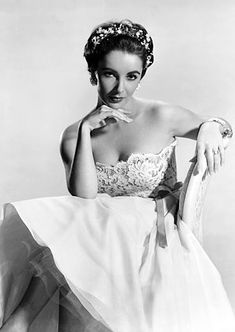 1956-Actress Elizabeth Taylor is shown seated, wearing a wedding gown-like dress and a pretty tiara. (Underwood )