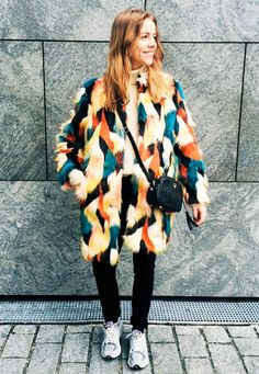 Street style look maxi casaco peludo colorido, calça preta, tênis e bolsa pequena preta.