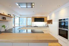 Wohnküche weiß hochglänzend mit Barboard in Eiche. U-Form geplant von unseren Küchenspezialisten.