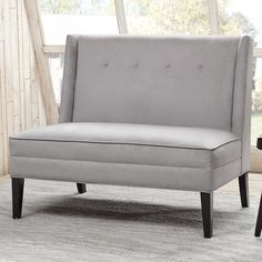 This modern settee with its button tufted detailing and high back provides maximum seating in minimum space. Featured in a silver gray color for a modern update.