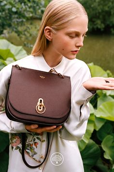 Shop the Amberley Satchel in Oxblood Leather at Mulberry.com. Inspired by British countryside pursuits, the Amberley gets its ring hardware and satchel shape from traditional equestrian styling. This smaller satchel features a geometrical rider's lock closure in brass hardware, inspired by and reinterpreting the centre of the iconic postman's lock. Inside it is luxuriously finished with a suede lining. Multi-functional, it can be worn over the shoulder or across body.